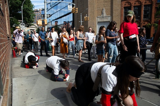 """Pope.L, """"Conquest,"""" 2019. A group crawl featuring 140 participants, 5-hour duration. Commissioned by Public Art Fund and presented on September 21, 2019 in Downtown Manhattan, New York City © Pope.L Photo credit: Timothy Schenck, courtesy of the artist and Public Art Fund"""