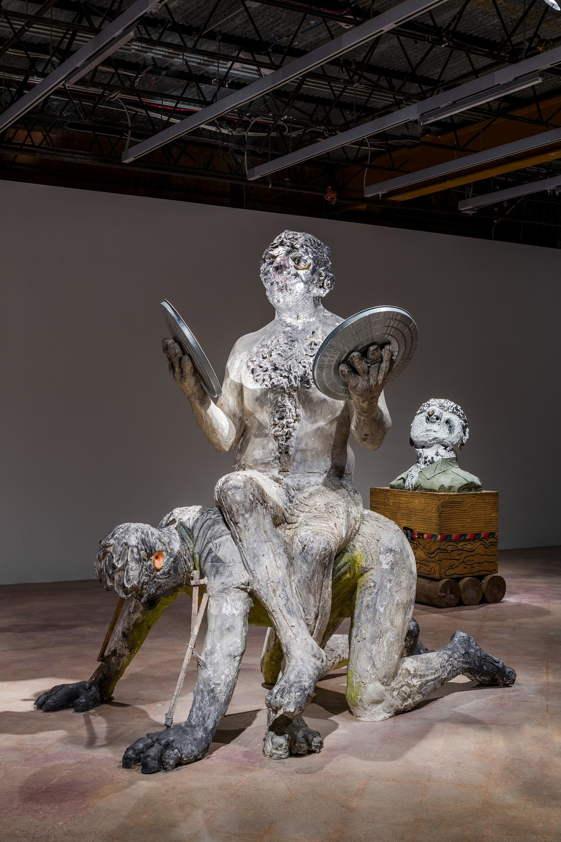 "Nicole Eisenman """"Man at the Center of Men,"" plaster version,"" 2019 Plaster, foam, fiberglass, epoxy resin, graphite, trashcan lids, mirrors, silver leaf, wood, and paint 97 x 100 x 64"" [HxWxD] (246.38 x 254 x 162.56 cm) Approx. Inventory #EIS549 Courtesy of the artist and Vielmetter Los Angeles"