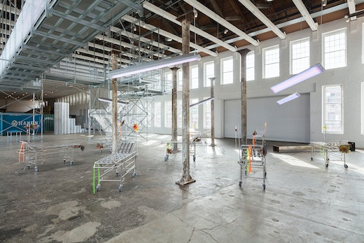 """Liz Glynn """"Post-industrial Vacationland (After Aldous Huxley),"""" 2017 Reclaimed cast-iron columns, selections from the """"Neverwork"""" series (modified stainless steel gurneys and aqua-resin) and the """"Desert Future"""" series (cast stainless steel tumbleweeds), and tanning lamps, dimensions variable"""