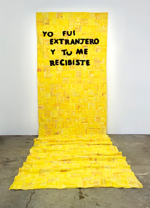 This is an artwork titled Quilt of Radical Hospitality / Edredón de hospitalidad radical by artist Andrea Bowers made in 2008
