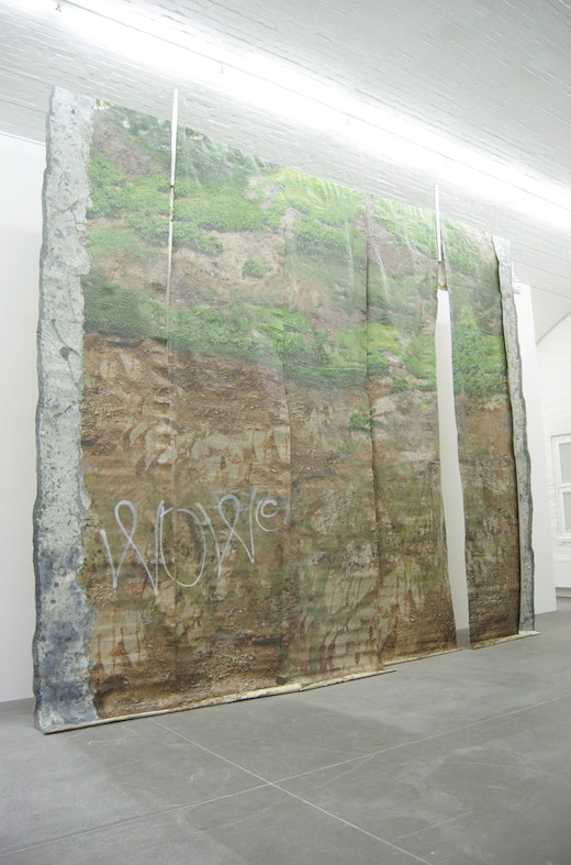 """Ruben Ochoa """"Remnants of a Fwy Wall Extraction/ Wallpaper with the Sounds of its Own Removal,"""" 2006/ 2008 Digital print, spray paint, acrylic on vinyl wallpaper, wall paper paste, concrete, fencing posts, steel cables, 55 minute CD with sound Variable dimensions (7 strips, each approx 8 m x 1.2 m)"""