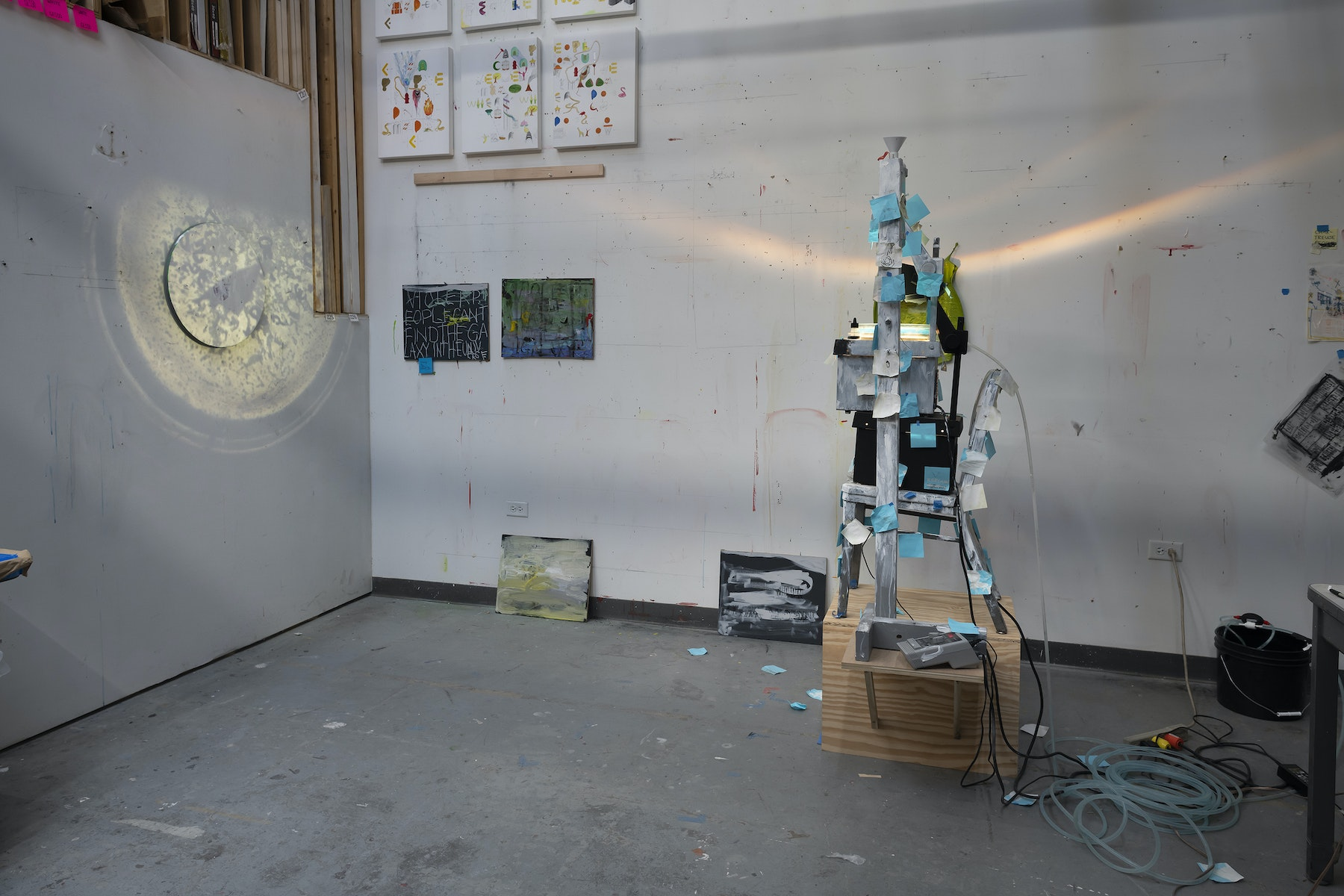"Pope.L ""I Machine,"" 2014 - 2020 (2) overhead projectors, acrylic and graphite on canvas, speakers, microphone, chair, post-its, solenoid, tubing, gralab 451 photo timer, (2) glass trays, funnel with container, wooden box, wooden armature, painter's tape, threaded rod, bucket 79.5 x 36 x 30"" [HxWxD] (201.93 x 91.44 x 76.2 cm) Inventory #POP345 Courtesy of the Artist and Vielmetter Los Angeles. © Pope.L Photo credit: James Prinz"