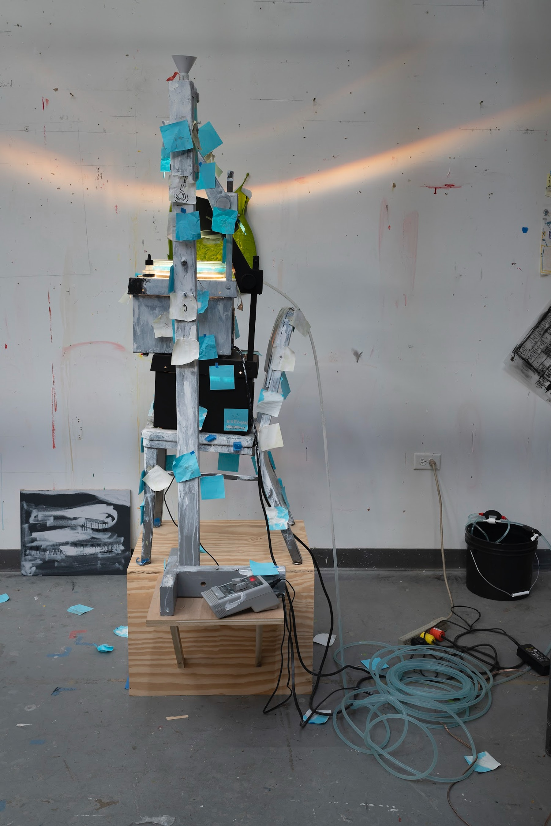 """Pope.L """"I Machine,"""" 2014 - 2020 (2) overhead projectors, acrylic and graphite on canvas, speakers, microphone, chair, post-its, solenoid, tubing, gralab 451 photo timer, (2) glass trays, funnel with container, wooden box, wooden armature, painter's tape, threaded rod, bucket 79.5 x 36 x 30"""" [HxWxD] (201.93 x 91.44 x 76.2 cm) Inventory #POP345 Courtesy of the Artist and Vielmetter Los Angeles. © Pope.L Photo credit: James Prinz"""